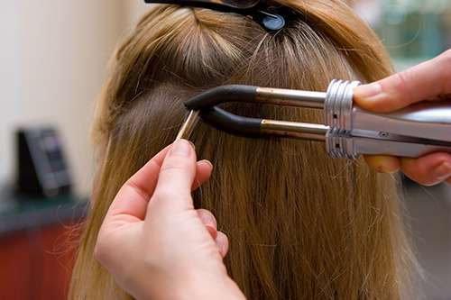 Professional hair extensions being applied